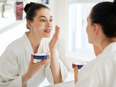 Beautiful young woman with cream for her face looking in the mirror in bathroom at home. Facial treatment. Cosmetology, beauty and spa.